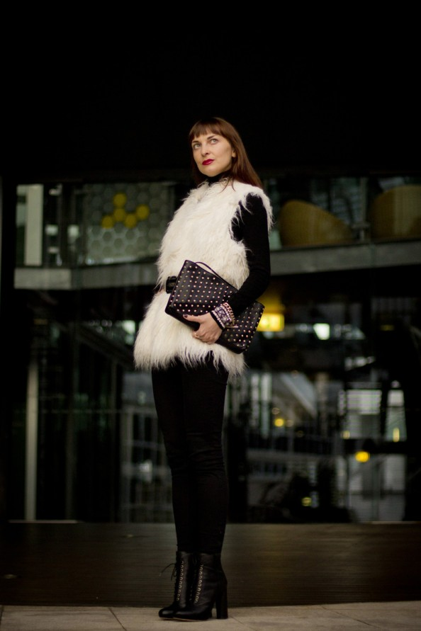 white fur vest and studded clutch