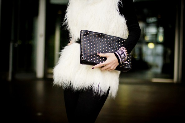 white white faux fur vest and studded leather clutch