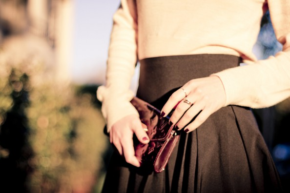delicate gold rings and dark cherry nails and louis vuitton clutch